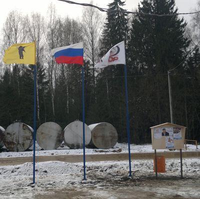 На флагштоках флаги России, области и предприятия